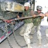 1200px-US_Navy_030730-N-9455K-103_Seabees_use_a_breaker_bar_to_secure_a_bulldozer_before_transporting_it_to_Camp_Moreell_from_Camp_Castle